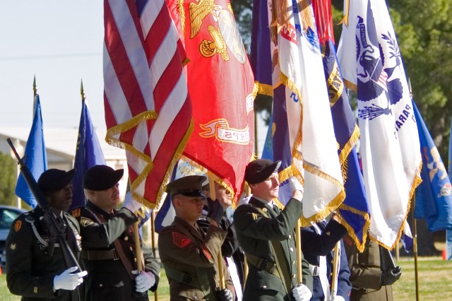 A Soldier in the multi-service color guard stands out front holding the Army colors during the Fort Bliss Veterans Day celebration Friday at Memorial Circle.