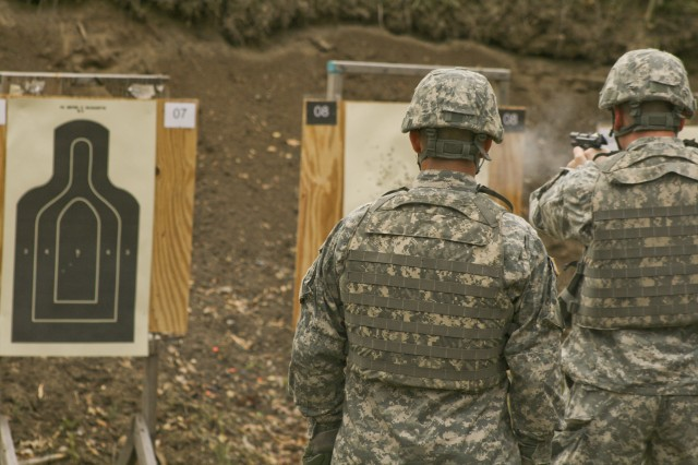 A U.S. Army Sustainment Command Soldier fires during M9 Pistol qualification as range safety and firing coach, Staff Sgt. Jeffry Smith watches. The Soldiers qualified at Klaes-Tralau Memorial Range near Shaffton, Iowa, about 20 miles north east of Rock Island Arsenal Nov. 7. Soldiers of ASC manned the range during the week to support the command's training requirements on the M9 Pistol and the M16A2 Rifle.
