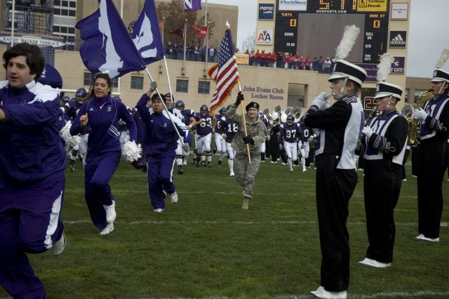 Staff Sgt. Wendy Johnson, Illinois Army National Guard, 404th Chemical Brigade, carries the American flag into Ryan Stadium while leading members of the Northwestern University football team onto the field in celebration of Veterans Day in Evanston, Ill. November 8, 2008.