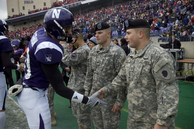 Sgt. Jordan Nechkash, Illinois Army National Guard, and Pfc. Giovanni Sciortino, Illinois Army National Guard, are congratulated by members of the Northwestern University football team.  Nechkash and Sciortino participated as Northwestern University\'s honorary captains in honor of Veterans Day in Evanston, Ill. November 8, 2008.