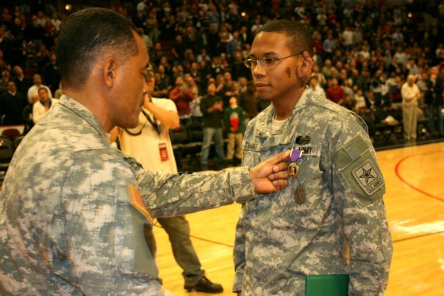 Lt. Col. Reginald Truss, U.S. Army Reserves, 416th Engineer Command, presents his Little Brother, Staff Sgt. Redus Thomas, Chicago Recruiting Battalion, with his second Purple Heart during the Chicago Bulls Veterans Day game. Thomas received his latest Purple Heart when his truck struck an improvised explosive device in Iraq Oct. 19, 2005. Thomas returned to his burning and exploding truck 3 times while wounded to pull his fellow soldiers to safety. Two of those soldiers died of their injuries.