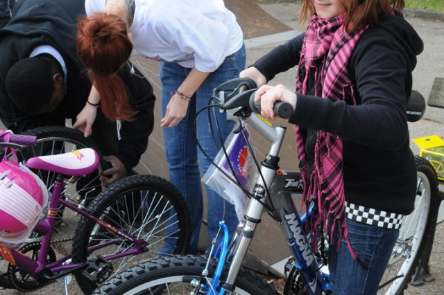 A child from the Parsberg children's home inspects a new bike donated to the home while two volunteers from U.S. Army Garrison Hohenfels, Germany, work to inflate tires on the other bikes. As part of Hohenfels' first organized Make a Difference Day, the community donated toys and equipment, including 18 bikes.
