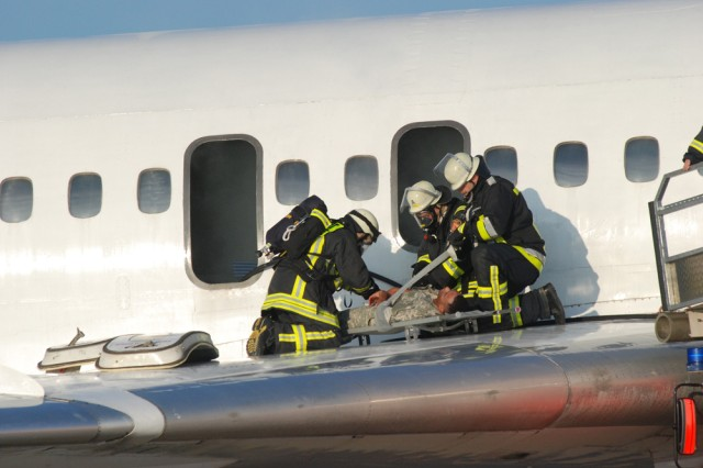 "After rescuing a ""trapped passenger,"" Stuttgart Airport firefighters strap the victim onto a stretcher. The action was part the Stallion Shake 2008 exercise conducted by U.S. Army Garrison Stuttgart, Germany"