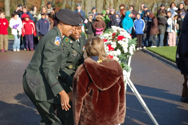 USAG Schinnen Commander, Lt. Col. Fern Sumpter (L) and Command Sgt. Major Mary Brown (R) help students from Geilenkirchen Elementary and AFNORTH International School lay a wreath at the American Military Cemetery in Margraten, Netherlands to commemorate Veterans Day 2008.