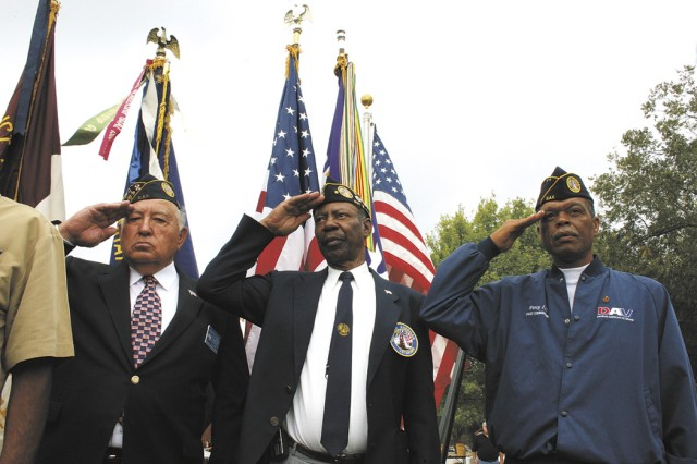 Disabled American Veterans Leonard Ruiz, Harold Williams and Percy Spence salute the passing colors during the Veterans Day ceremony Nov. 11 at the Fort Sam Houston National Cemetery. Several hundred people attended the annual two-hour observance.
