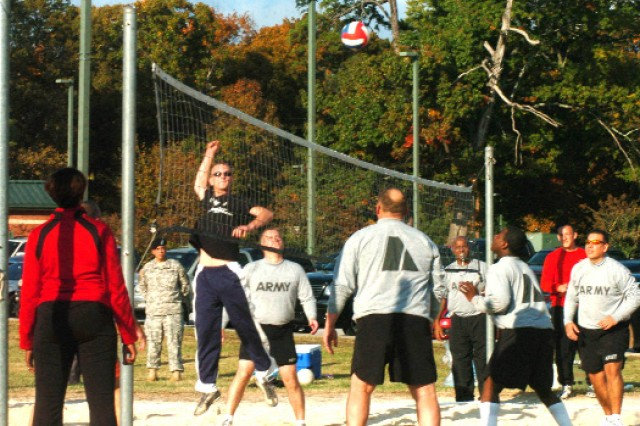 Sgt. Michael Marzoll, combat engineer, USARCENT G-7,  spikes the ball over the net as Soldiers from Headquarters and Headquarters Company's team attempts to block it during the championship volleyball game held Nov. 3 on Fort McPherson.  ""