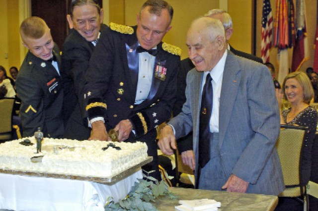Following tradition, Lt. Gen. James Lovelace (center), commander, U.S. Army Central (USARCENT), cuts the unit's birthday cake during the ball held Nov. 7 in Atlanta in honor of USARCENT's 90th anniversary.  Helping, from left, are the unit's youngest Soldier, Pvt. Steven Schanstra, USARCENT operational protection early warning missile system operator,  and George Kottwitz and Dalton Mathis, both distinguished World War II veterans who served in Patton's Third Army. Former Third Army commander, Lt. Gen. (Ret.) Steven Arnold (face not seen), also served as the distinguished speaker for the evening. ""