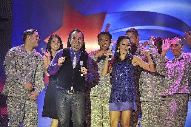 Victor Hurtado (front with microphone), reigning Operation Rising Star Spc. Richard Sianoya (center) of Fort Irwin, Calif., and host GeNienne Samuels, a former Washington Redskins Cheerleader, dance with the finalists in the 2008 Operation Rising Star military singing contest Oct. 13 at Wallace Theater on Fort Belvoir, Va.