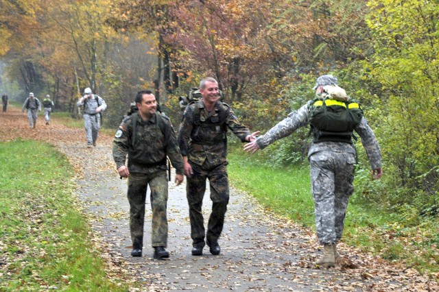 Sgt. Mark McClanathan of the 43rd Signal Battalion (right) extends a handshake to German Airman 1st Class Hans Ettelbrueck, Polycone Air Defense Unit, during a 25-kilometer rucksack march that is part of qualifying for the German Armed Forces Badge for Military Proficiency, in Niedermohr, Germany, Nov. 6.