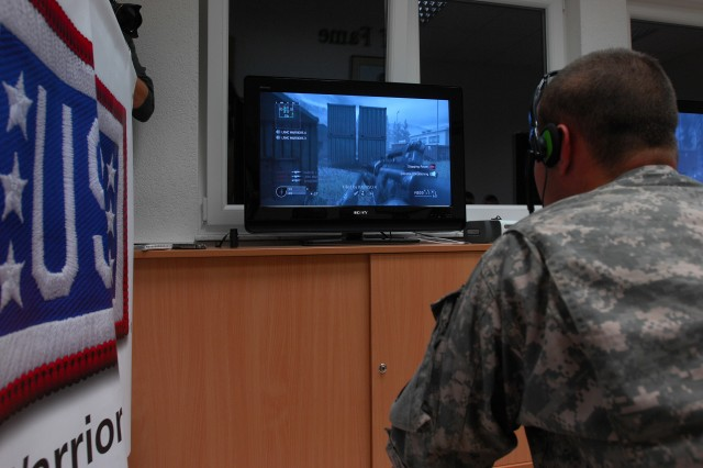 Spc. Justin Lara competes against NFL players from the Tampa Bay Buccaneers and fellow servicemembers from Dubai, Japan and Kuwait in a game of Call of Duty: World at War on Veteran's Day at the USO Warrior Center at Landstuhl Regional Medical Center, Germany. Lara is a 19-year-old native of Tucson, Ariz., receiving treatment at LRMC while deployed with the 101st Airborne Division in Afghanistan.