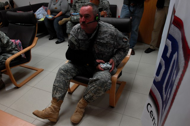 Sgt. Steve Webb competes against NFL players from the Tampa Bay Buccaneers and fellow servicemembers from Dubai, Japan and Kuwait in a game of Call of Duty: World at War on Veteran's Day at the USO Warrior Center at Landstuhl Regional Medical Center, Germany. Webb is a 45-year-old New Jersey Army National Guardsman receiving treatment LRMC while deployed to Iraq.