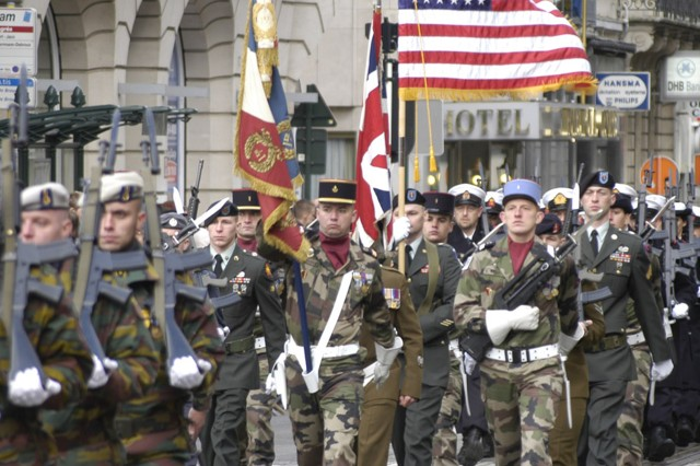 The Anglo-French-U.S. Color Guard, preceded and followed by Belgian contingents, marches down the Rue Royal in downtown Brussels on the 90th Anniversary of Armistice Day.