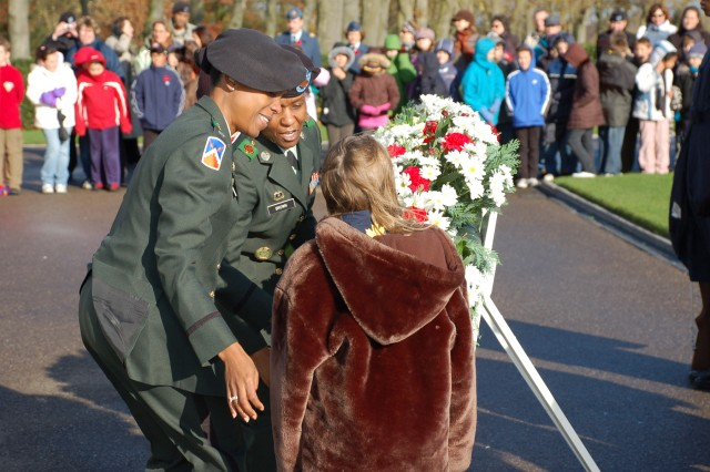 USAG Schinnen Commander, Lt. Col. Fern Sumpter (L) and Command Sgt. Major Mary Brown (R) help students from Geilenkirchen Elementary and AFNORTH International School lay a wreath at the American Military Cemetery in Margraten, Netherlands, to commemorate Veterans Day 2008.