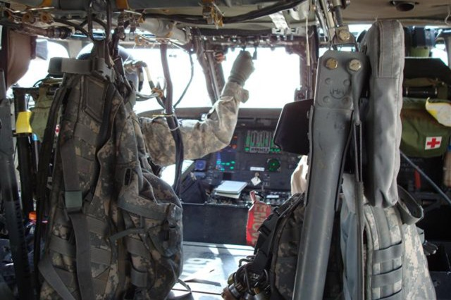 A Soldier performs an engine run-up in preparation for a UH-60 air transport mission. Aircraft survivability equipment (APR-39 and CMWS) is on and operational as visible in the instrument panel.