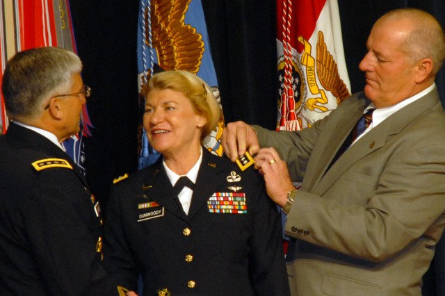 Chief of Staff of the Army Gen. George W. Casey Jr. pins the fourth star on Gen. Ann E. Dunwoody during a ceremony at the Pentagon, Nov. 14. Casey is assisted by Dunwoody's husband, Craig Brotchie.
