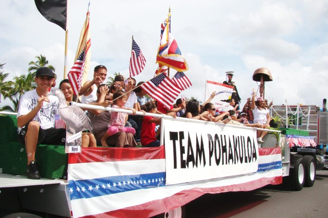 HILO, Hawaii - Pohakuloa Training Area (PTA) employees and family members wave from their float to crowds along Kamehameha Avenue, in Hilo, during a Veterans Day Parade, Nov. 8. The bronze-colored memorial to a fallen warrior was sculpted from chicken wire and paper mache by PTA employees.