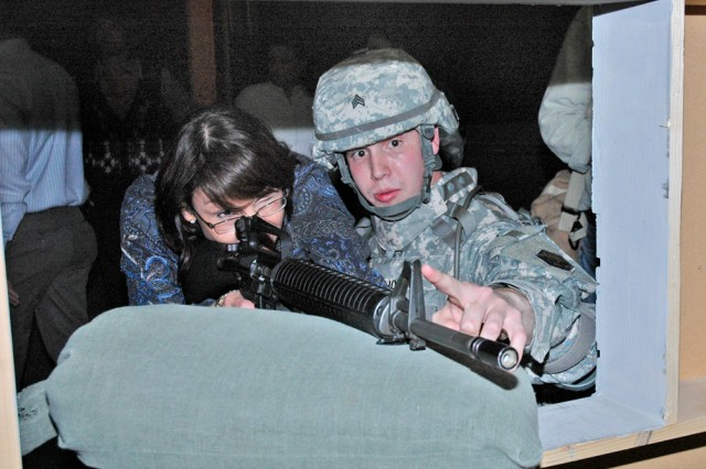 Sgt. Jeffrey Holder of Company C, 1st Military Intelligence Battalion, shows Hainerberg second-grade teacher Gloria Knauf how to site a target in the Engagement Skills Trainer during a demonstration at U.S. Army Garrison Wiesbaden, Germany. The military orientation demonstrated to Department of Defense Dependents Schools teachers and administrators what Soldiers experience while deployed.