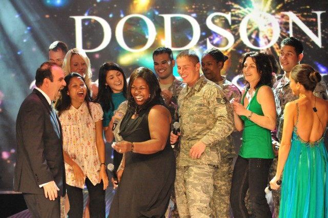 Army family member and veteran Joyce Dodson (black dress with microphone) of Bamberg, Germany, receives the adoration of finalists after winning the 2008 Operation Rising Star military singing contest Nov. 14 at Wallace Theater on Fort Belvoir, Va.