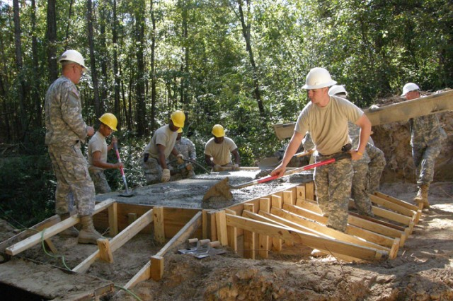 Now that six yards of concrete is in the form, National Guardsmen work together to spread and level it.