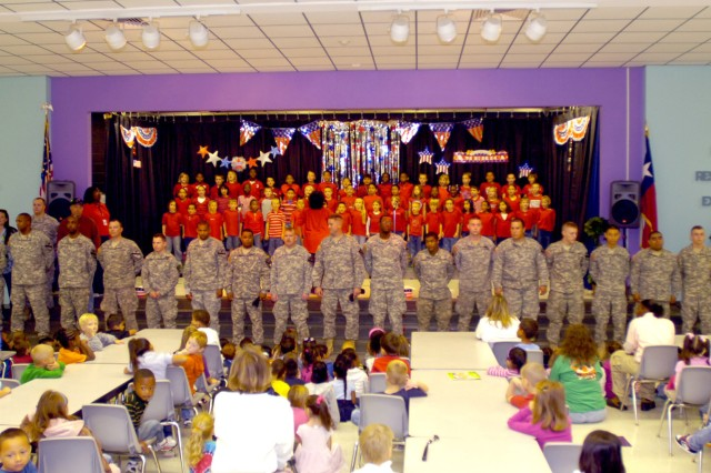 """While the performers sing the song """"Thank a Vet,"""" all veterans in attendance stand to be honored in front of the students, faculty, and family members at the Venable Village Elementary School on Fort Hood, Texas Nov. 7."""