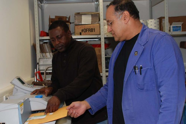 According to customer service trainer Pamela Robinson, co-workers such as Charles Yeborah, left, and Carlos Negron, clerks at the Kelley Barracks Official Mail Room, are expected to give each other the same courtesy and respect as they would give a customer at U.S. Army Garrison Stuttgart, Germany.