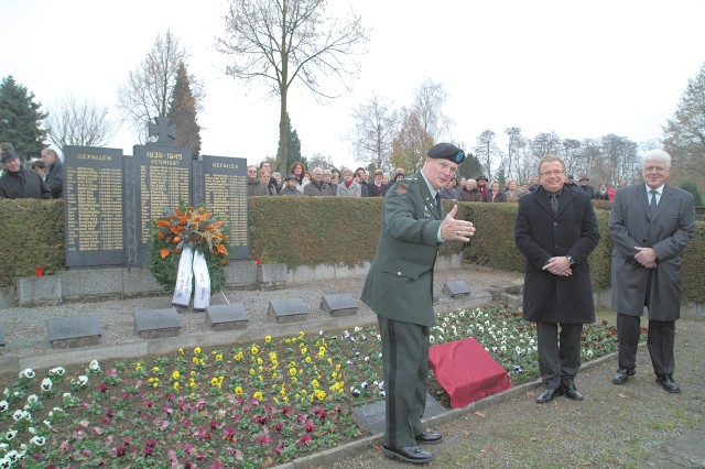 Chaplain (Lt. Col.) Joel Harris motions to Perry Blake and Sandra Salm, to sing a gospel duet before he, Sinsheim Mayor Rolf Geinert, and Dühren Mayor Walter Zahn unveil a memorial plaque to 21 American Soldiers who died in fighting in Dühren between April 1 and 3, 1945. The memorial unveiling was part of Volkstrauertag, a national day of mourning held Nov. 16. The unveiling followed a ecumenical church service, and a bilingual memorial ceremony.
