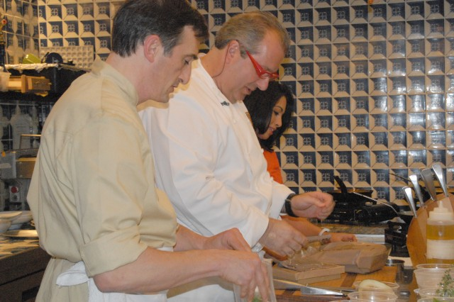 Chef Roberto Donna (center) and Sous Chef Claudio Sandri go through one of their MREs as Soldiers Radio and Television's Ana Allen looks on. The chefs didn't know all of the ingredients in the MREs until the mission started. Then they had 30 minutes to cook.