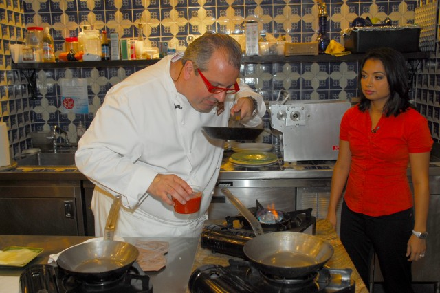 Ana Allen of Soldiers Radio and Television looks on as Chef Roberto Donna smells the sauce he made for a Mission: MRE dish.