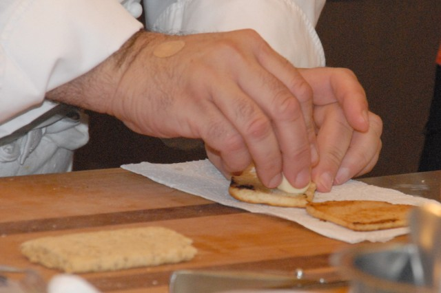 Chef Roberto Donna turns MRE flatbread into toasted garlic bread to accompany his chicken parmesan.