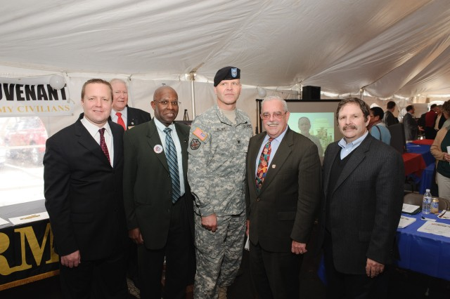 Fairfax County, Va., resident Lt. Col. Maura Gillen, on movie screen at right, sends best wishes and appreciation to Northern Virginia military and civilian leaders on the occasion of the Army Community Covenant celebration Nov. 15 in Woodbridge. From left are Chairman Corey Stewart, Prince William County Board of Supervisors; Supervisor John Jenkins, Neabsco District, Prince William County; Dr. Sam Hill, Provost, Woodbridge Campus, Northern Virginia Community College; Col. Jerry L. Blixt, Installation commander, Fort Belvoir; Congressman-Elect and Board Chairman Gerry Connolly, Fairfax County; and, Miles Friedman, Senior Principal, Miles Friedman & Partners, LLC. Hill and Friedman are co-chairs of the Quantico-Belvoir Regional Business Alliance, whose purpose is to enable support for the military community in the region, hosted the event. More than 300 people turned out to enjoy food, game, exhibits and demonstrations. Videotaped messages from Northern Virginia Soldiers based in Iraq and Afghanistan were played continuously, conveying the Soldiers' greetings to their Families, and their appreciation for community support of the covenant and the military.