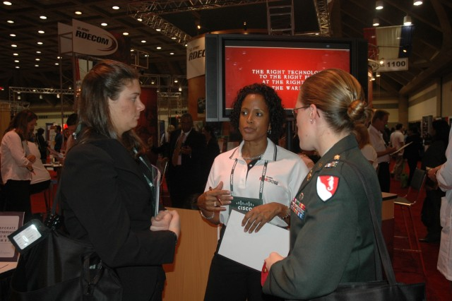 Gayla McMichael, (middle) an engineer for the Aviation and Missile Research, Development and Engineering Center, discusses career opportunities with student attendees during the career fair at the Society of Women Engineers conference.