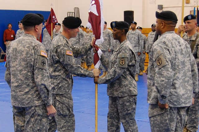 Lt. Col. Timothy P. Albers (center left) passes the guidon during a redesignation ceremony for the former Warrior Transition Unit, now called the Warrior Transition Battalion. The ceremony was held at the 1st Maneuver Enhancement Brigade Gym Nov. 12. The unit's mission is to provide command and control for  Soldiers who have suffered injury or illness and ensure they receive appropriate medical care and administrative support.