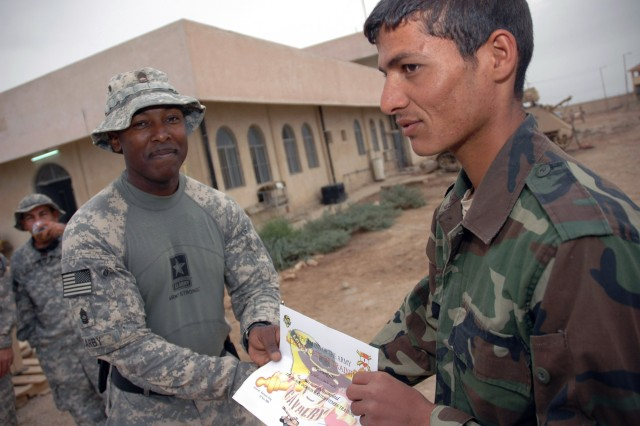 Master Sgt. Juan Darby from Tampa, Fla., hands an Iraqi soldier the first certificate of achievement for completing the Black Dragon Master Fitness Course Nov 10.