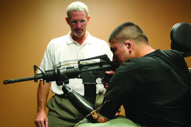 Ross Colquhoun, a firearms instructor, helps SPC Marco Robledo learn to fire an M-4 rifle with his prosthesis during opening of the Military Advanced Training Center at WRAMC in 2007.