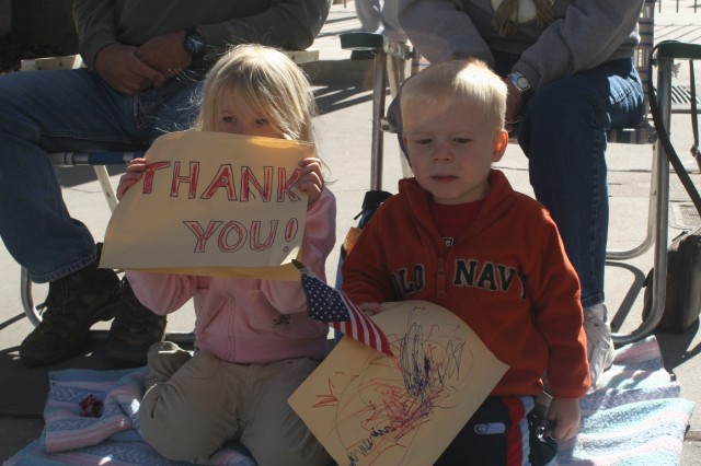 Kaelyn Blessinger, 4, and her little brother A.J., 2, display tokens of their thanks during the Veterans Day Parade in downtown El Paso.