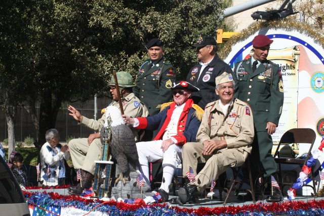 """Members of the Roy P. Benavidez-Patterson """"All Airborne"""" Chapter of the 82nd Airborne Division Association dressed in Revolutionary War, World War II and current Army uniforms ride on their first-place float during El Paso's Veterans Day Parade. The organization's float won the parade's top prize for the fourth straight year."""