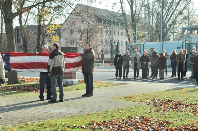 Former employees of the U.S. Army Garrison Hessen's Hanau Community fold the flag during a ceremony Nov. 18 on Pioneer Kaserne, Germany, marking the final closure of the installation.