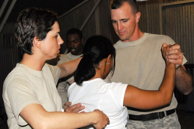 Sgt. Lucy Dunham instructs Army Staff Sgt. James Cowell and his partner on proper turning techniques during a salsa class on Camp Echo, Iraq.