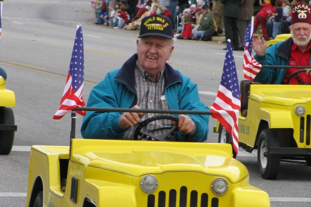 Parade crowds enjoyed the antics of Cahaba Shrine clowns, motorcycle riders and car drivers, such as this World War II veteran who is taking a spin in a yellow car representing the Marshall County Shriners. Several nearby counties had entries in Huntsville's parade.