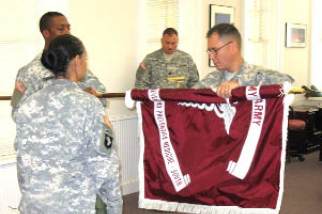 Staff members from the U.S. Army Center for Health Promotion and Preventive Medicine-South cases the unit\'s colors. Sgt. Thomas Strayhorn, color bearer and training and operations NCO, holds the flag as Lt. Col. Thomas Delk, commander, rolls it up before casing it as part of the ceremony signifying the unit's relocation to Fort Sam Houston, Texas, in 2009. Master Sgt. Martha Harris (left), unit NCO in charge, waits to case the command's flag as Capt. Shane Smith (center), industrial hygiene project officer, reads the orders.