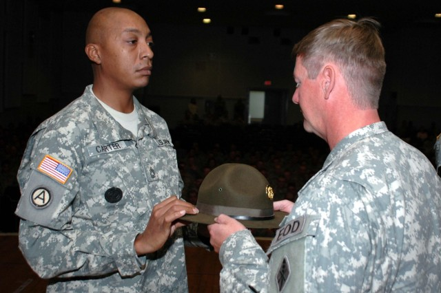 Sgt. 1st Class Gary Carter of Bravo Company, Explosive Ordnance Disposal Training Battalion (Provisional), hands his campaign hat to battalion Sgt. Maj. Randy Hefner, ending his term as drill sergeant and beginning his journey as platoon sergeant.