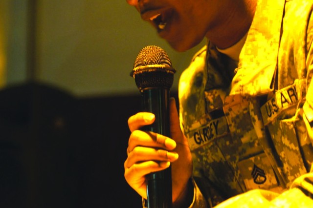 Sgt. 1st Class Reagan Gardley reads a poem during an open mike night at Camp Libery, Iraq.