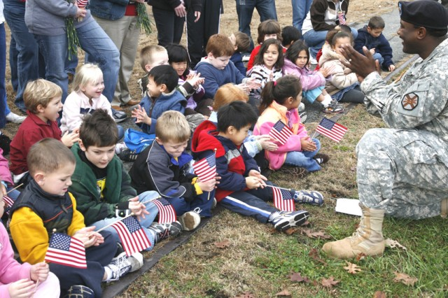 PICATINNY ARSENAL, N.J. - Children from the Picatinny Child Development Center sit with Picatinny chaplain assistant Sgt. Andre L. Gambrell near the fallen-heroes tree memorial area here Nov. 7. The children placed new flags at each of the trees in honor of the veterans and the Veterans Day holiday.