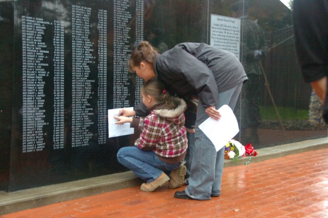 """Colette Textor helps her daughter Mckenna take a rubbing of her father's name on the 1st SFG (A) Memorial wall at Fort Lewis, Wash., following a Nov. 11 ceremony. """""""
