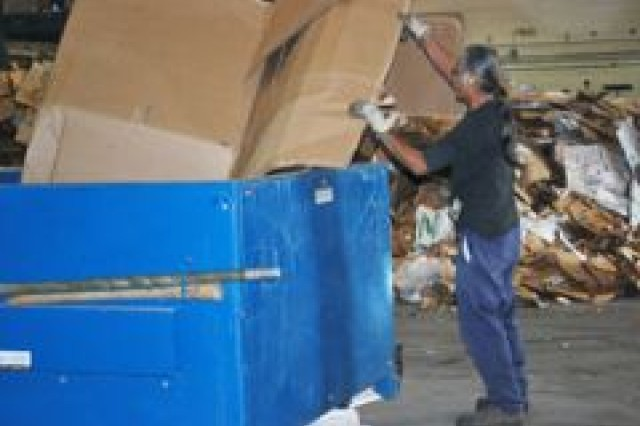 Workers lift a recyclable cardboard box. Eventually, the box will be baled and transported to a different recycle center where it will be made into a new product.