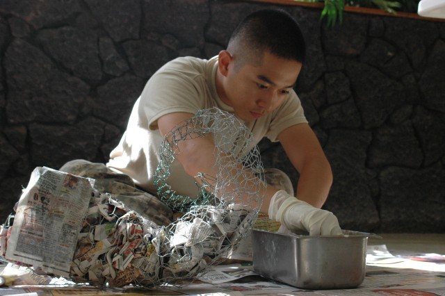 """WHEELER ARMY AIRFIELD, Hawaii - Pfc. Oliver Guzon, food service specialist, Headquarters Support Company, 209th Aviation Support Battalion, makes a small paper-mache cornucopia decoration for Thanksgiving Day at the Aviation Dining Facility (DFAC), here, Wednesday, Nov. 19. U.S. Army Garrison-Hawaii Soldiers from Wheeler Army Airfield, Schofield Barracks, and Fort Shafter DFACs are honing their culinary and decorative skills for a Thanksgiving Day competition to earn the title """"Best Army Dining Facility in Hawaii."""" The competition will ultimately decide which chefs will represent Hawaii at the Army's national competition at Fort Lee, Va., next year."""