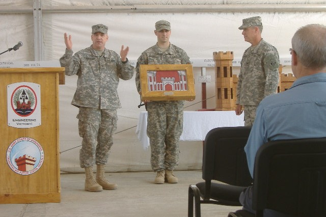 Col. Scott Donahue, left, director, Multi-National Corps-Iraq, C7, talks about the Corps' role in the success of the Coalition Munitions Clearance mission which ended Nov. 21. Col. Larry McCallister, right, commander, U.S. Army Engineering and Support Center, Huntsville, later accepted the cased flag for the CMC program from Donahue.