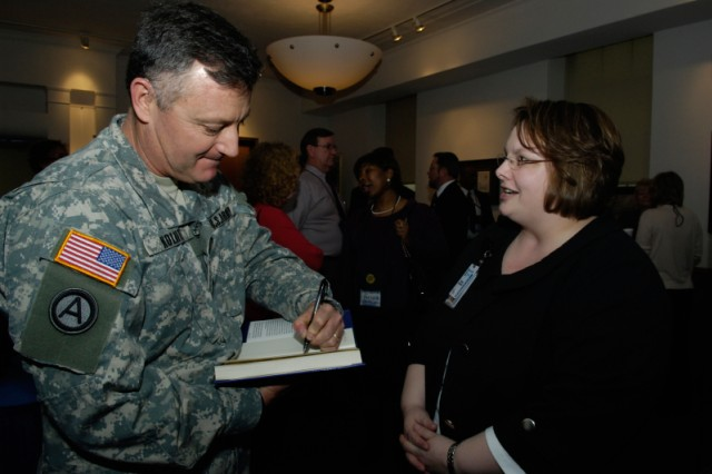 """Col. Thomas Kolditz, author of Aca,!A""""In Extremis Leadership: Leading as if Your Life Depended on It,Aca,!A? took the time to autograph his book for Fiona Burdick, Army Management Staff College faculty member during last yearAca,!a,,cs symposium."""