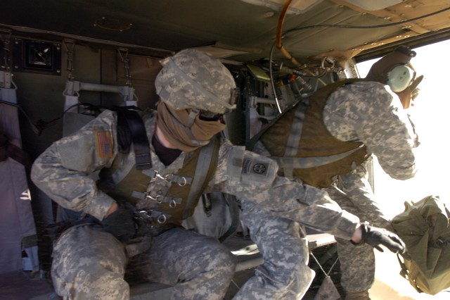 Two Paratroopers from the 407th Brigade Support Battalion, 2nd Brigade Combat Team, 82nd Airborne Division, toss a duffle bag from a UH 60 Blackhawk helicopter that's hovering 20 feet over the ground during speedball training on November 19.  Using speed balls, duffle bags full of supplies, is a quick and easy way to deliver supplies when they're unable to land the helicopter.  (U.S. Army photo by Sgt. Susan Wilt, 2nd BCT, 82nd Abn. Div. PAO)