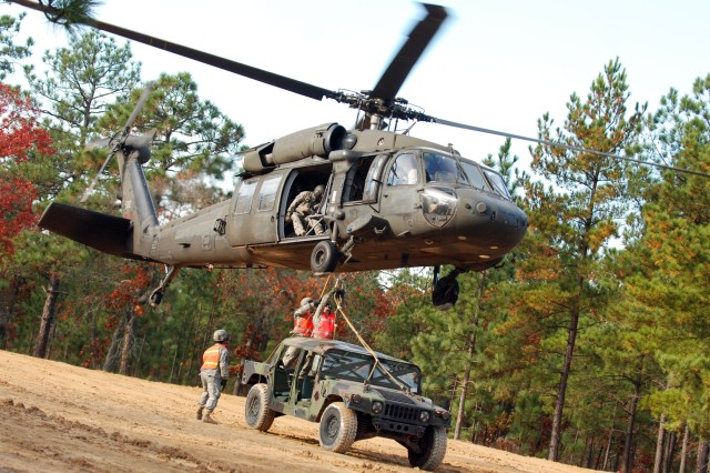 Two Paratroopers from the 407th Brigade Support Battalion, 2nd Brigade Combat Team, 82nd Airborne Division, attach a humvee by harness to the bottom of a UH 60 Blackhawk helicopter during sling load training on Nov. 17.  Sling load is a technique used to quickly move supplies to one area to another by helicopter.  (U.S. Army photo by Sgt. Susan Wilt, 2nd BCT, 82nd Abn. Div. PAO)